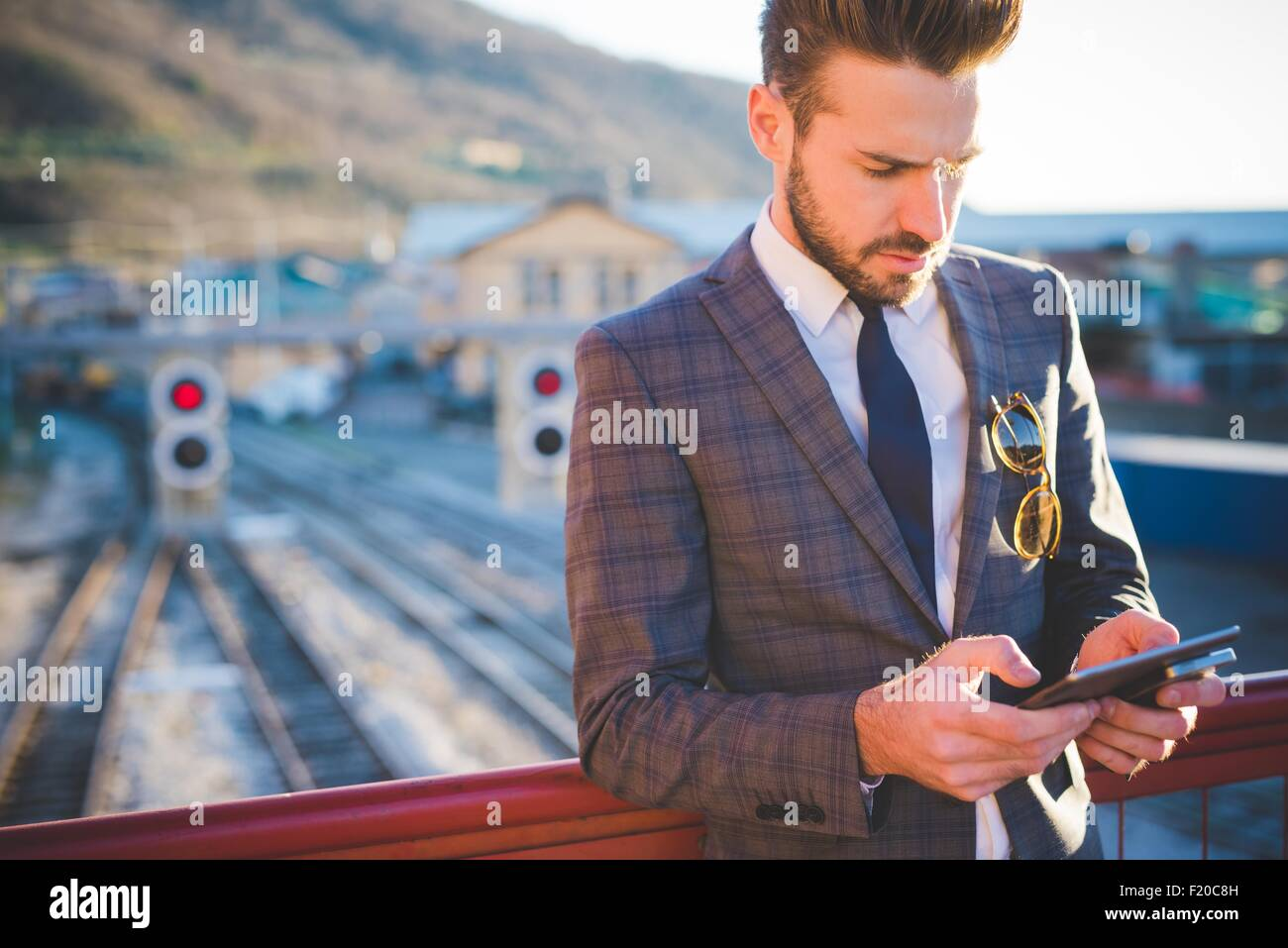 Young man with using digital tablet on railway footbridge - Stock Image