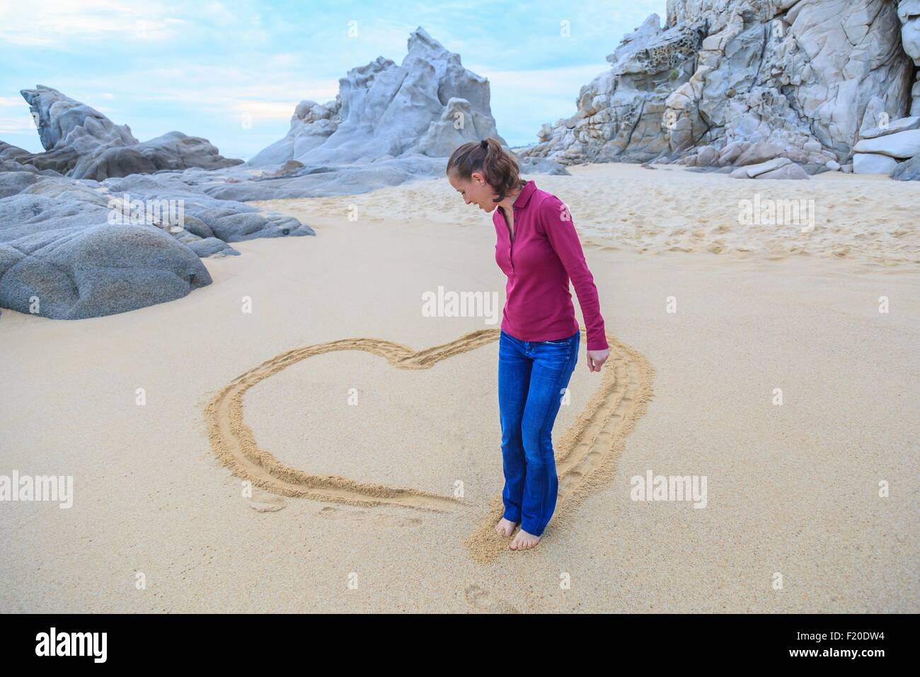 Mid adult woman on beach, drawing heart shape with feet - Stock Image