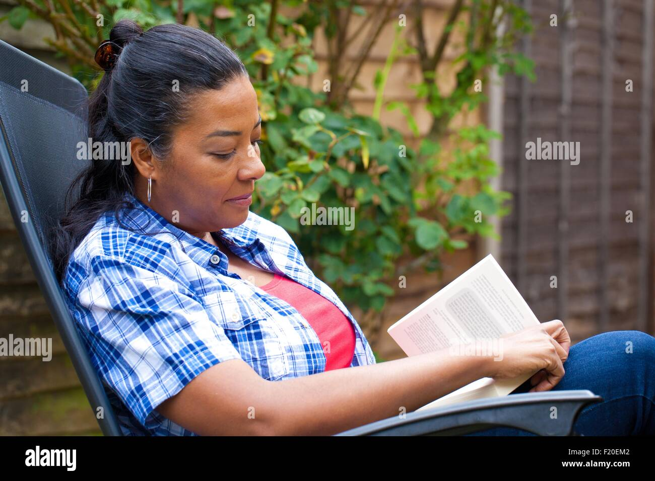 Mature woman on sun lounger reading book in garden - Stock Image