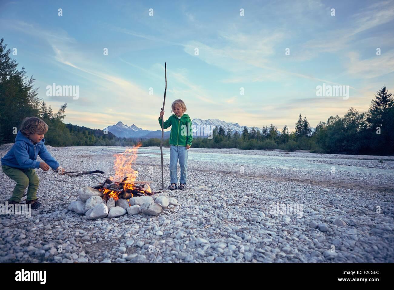 Boys poking campfire with sticks, Wallgau, Bavaria, Germany - Stock Image