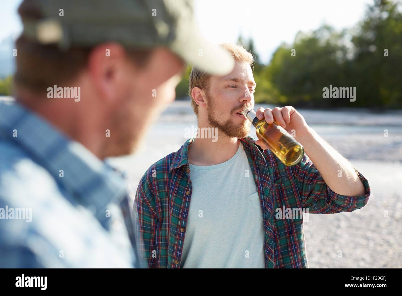 Young man taking a drink from a beer bottle, looking away - Stock Image