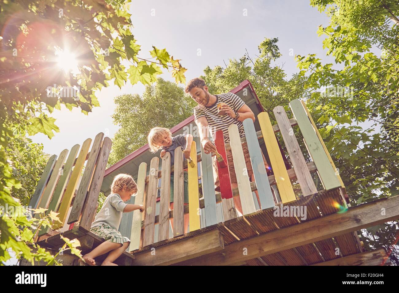 Father and two sons, painting tree house, low angle view - Stock Image
