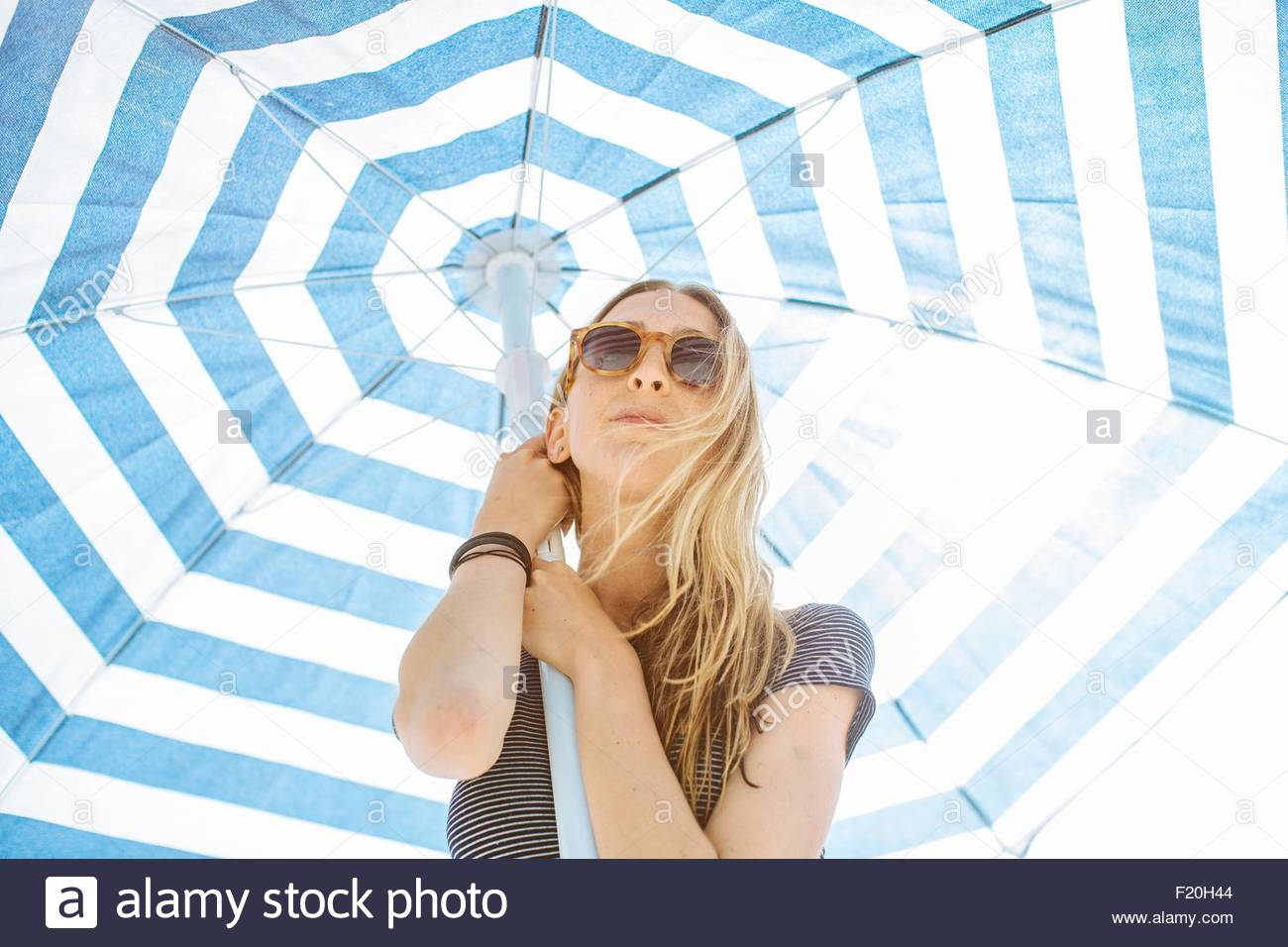 Low angle portrait of young woman holding up striped beach umbrella - Stock Image