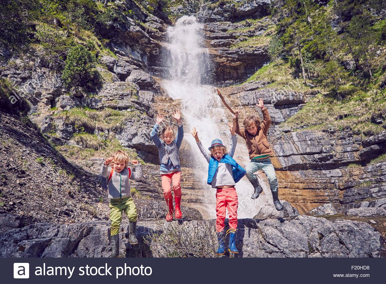 Group of children jumping off rocks by waterfall - Stock Image