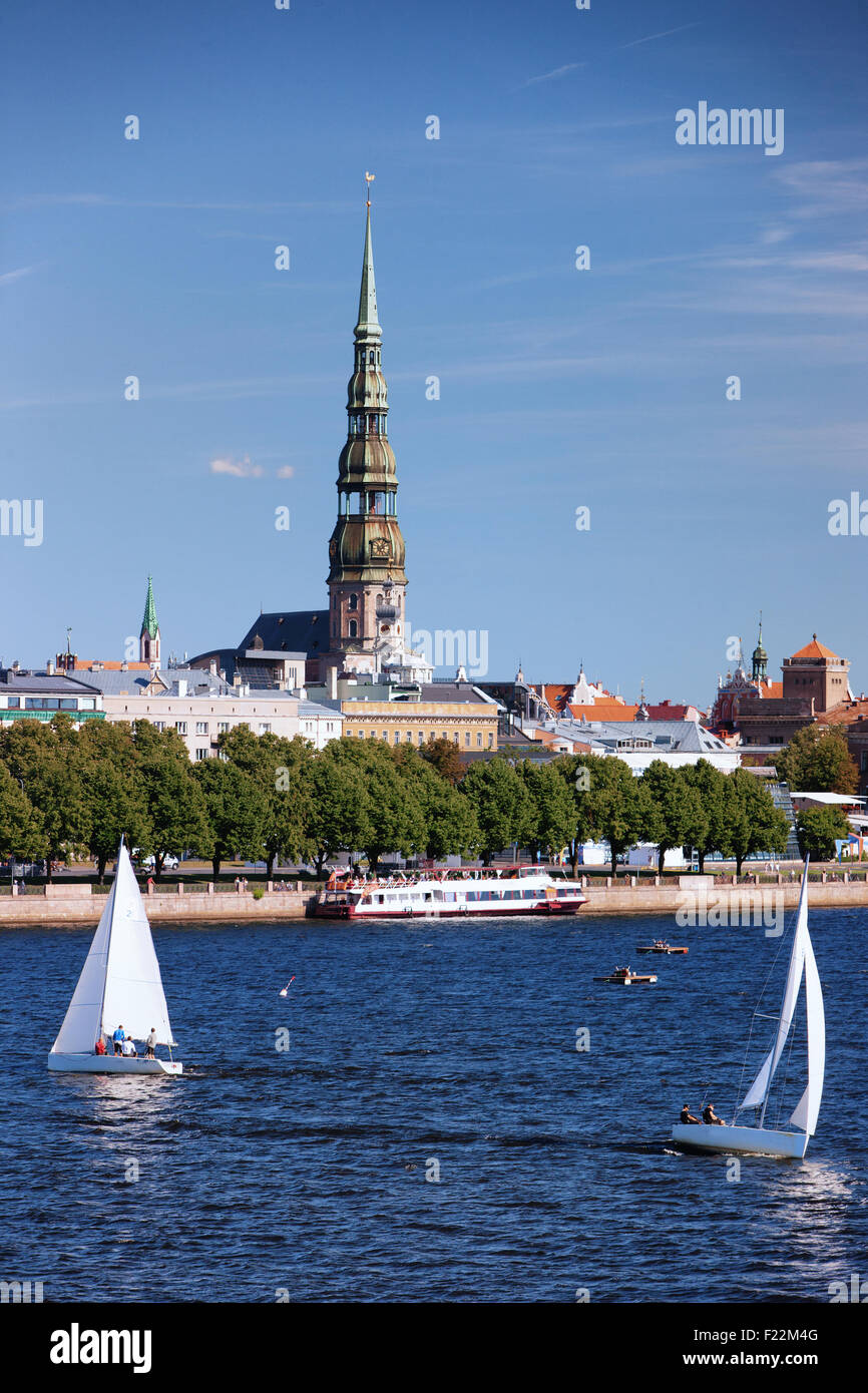 Latvia. Yachts with sails and a pleasure boat on the River Daugava in the background panorama with the church steeple - Stock Image