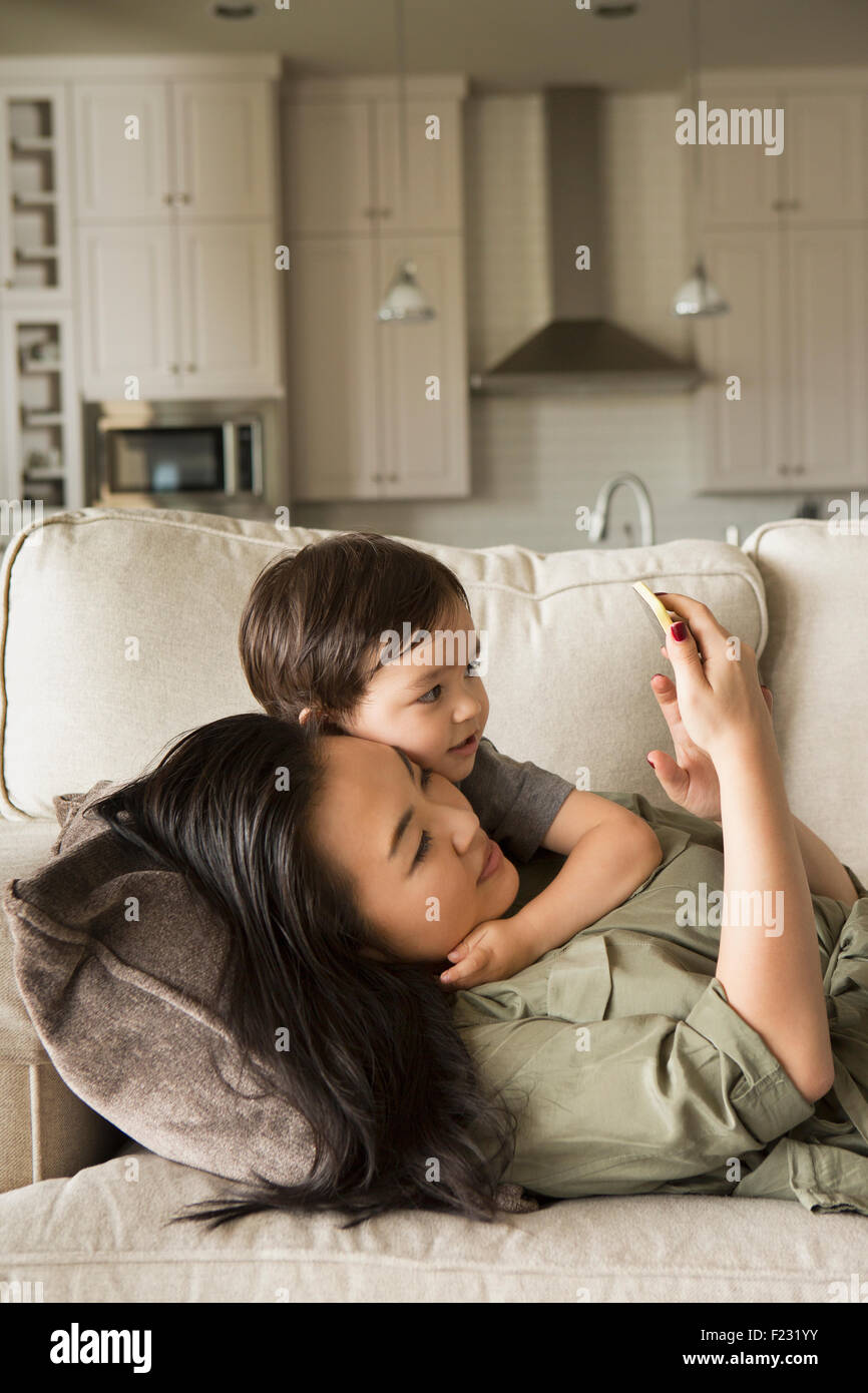 Woman lying on a sofa cuddling with her young son and looking at a cell phone. Stock Photo