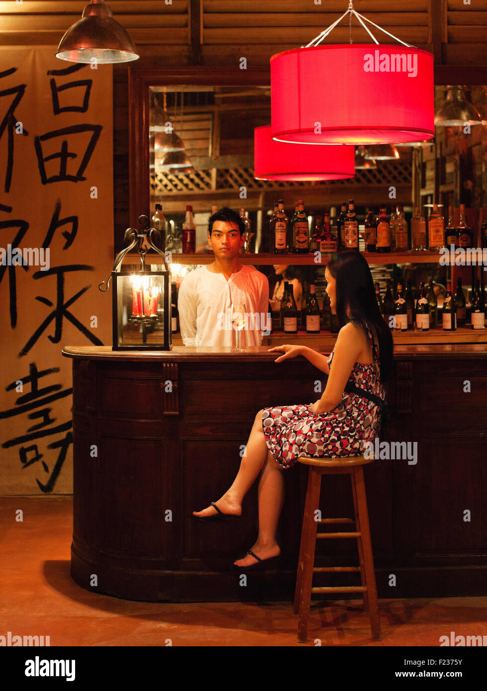 A woman drinks a cocktail at the Chin Chin Bar, Bon Ton Resort Langkawi, Malaysia. - Stock Image