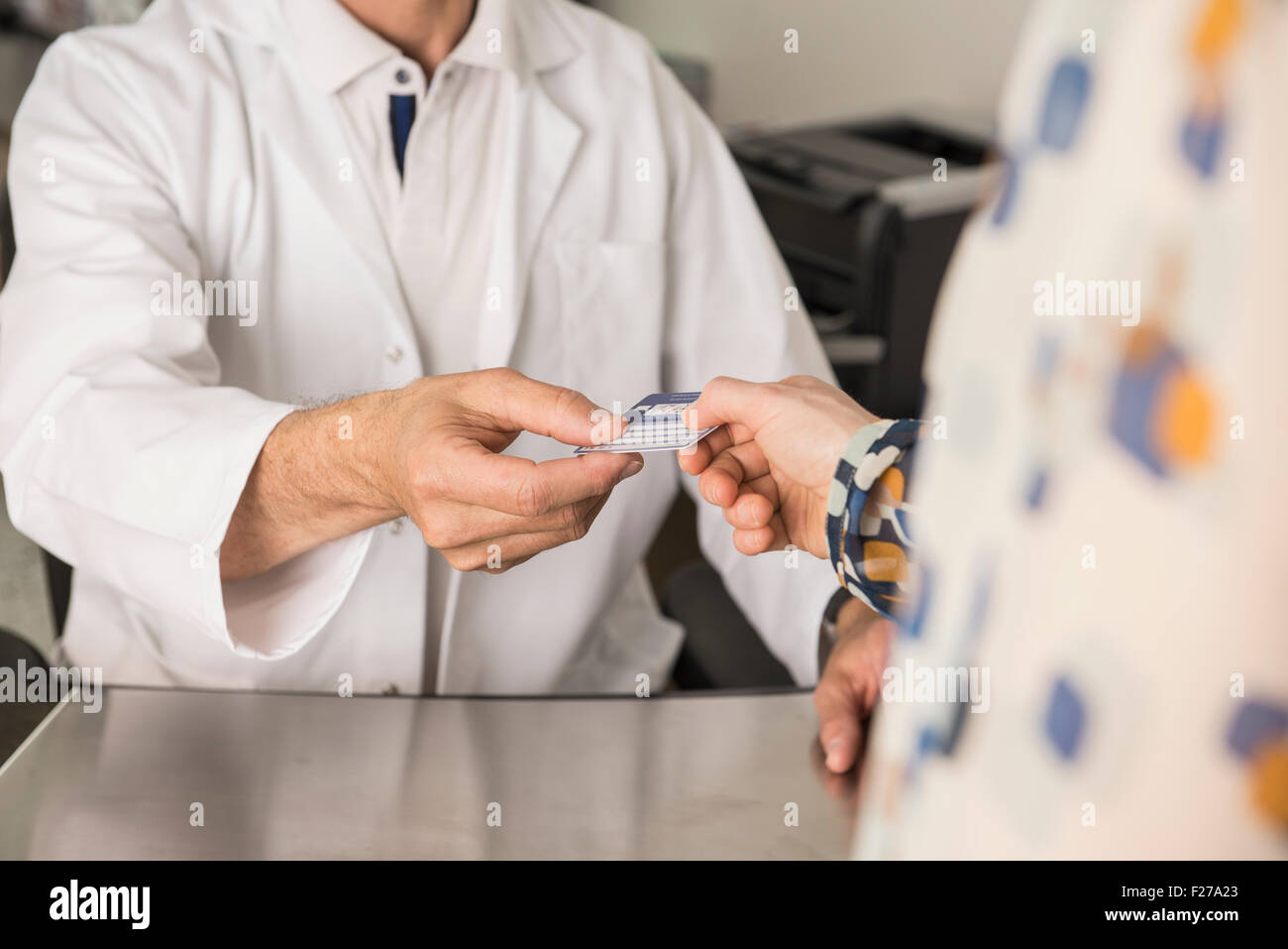 Patient giving a health insurance card to doctor, Munich, Bavaria, Germany - Stock Image