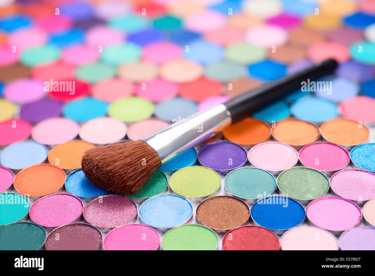 background with make-up brush and many multicolored eye shadows - Stock Image