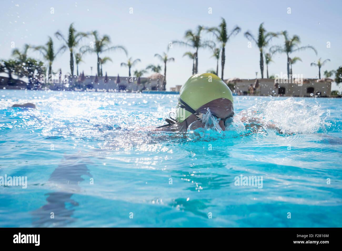 Mature woman swimming in swimming pool, Puglia, Italy - Stock Image