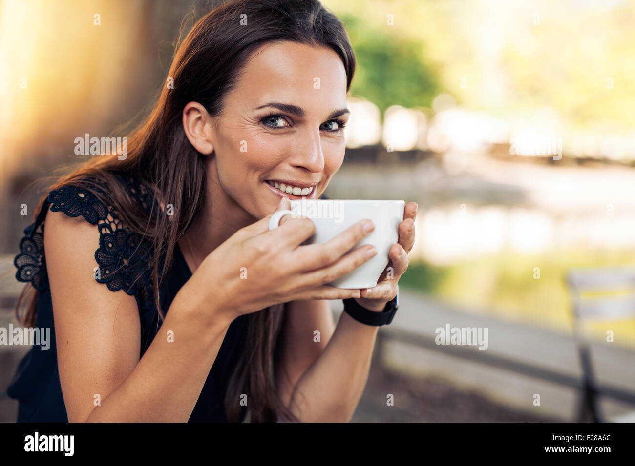Beautiful young woman holding a cup of coffee looking at camera smiling. Cheerful female enjoying a cup coffee at - Stock Image