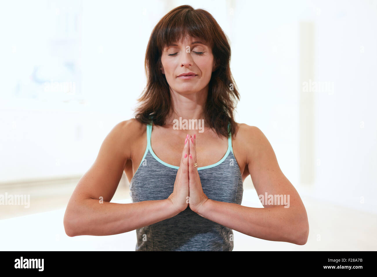 Portrait of a beautiful mature woman sitting in Anjali Mudra yoga pose at the gym meditating. Female fitness trainer - Stock Image