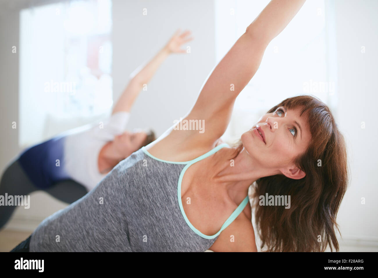Portrait of mature woman practicing yoga at gym. Fitness female doing Triangle yoga Pose, Trikonasana. - Stock Image