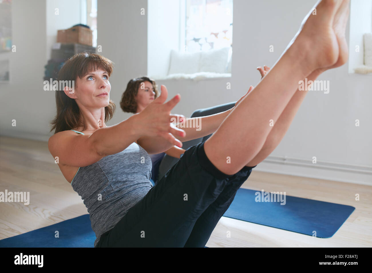 Women practicing stretching and yoga workout exercise together in a health club gym training class session. Two - Stock Image