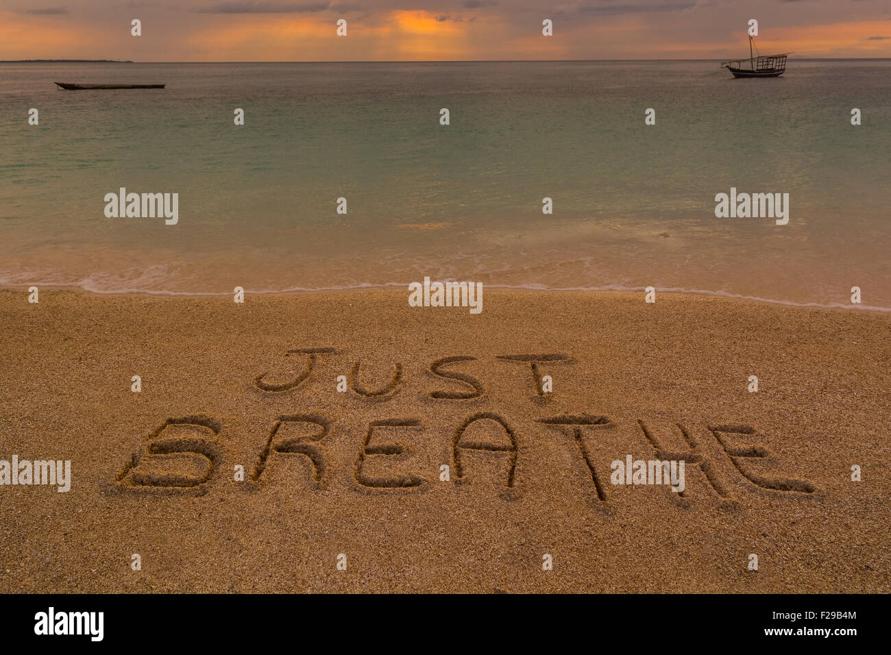 In the picture a beach at sunset with the words on the sand 'Just breathe'. - Stock Image