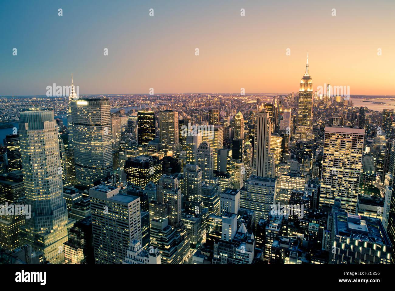 Beautiful New York City Manhattan buildings lit up at sunset - Stock Image