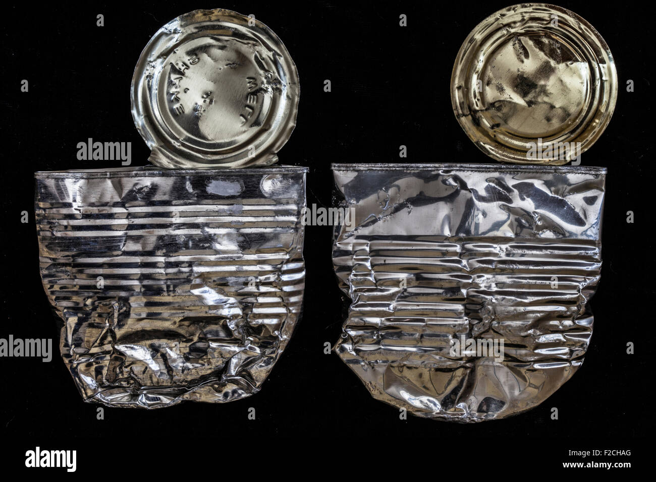 two flattened metal cans on black - Stock Image