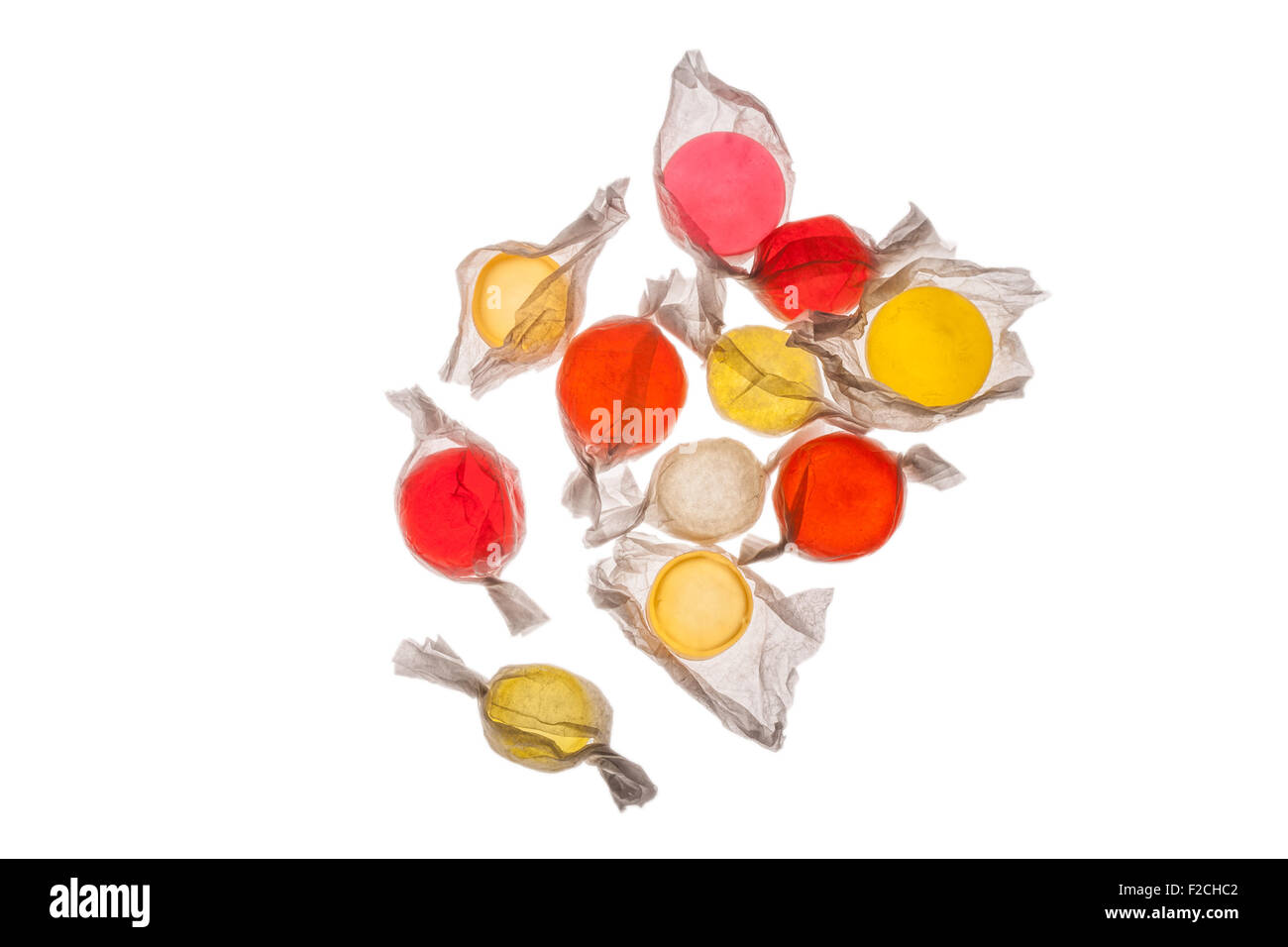 overhead view of orange, yellow, red, pink candy in wrappers on light table - Stock Image