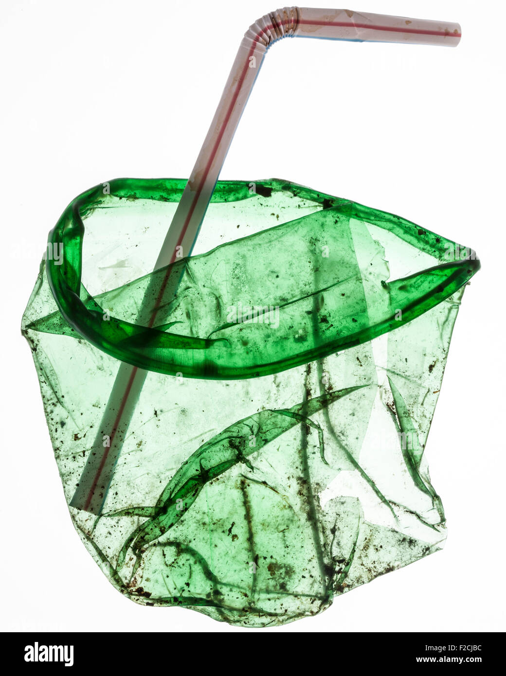 flattened, dirty green translucent plastic cup with bent straw - Stock Image