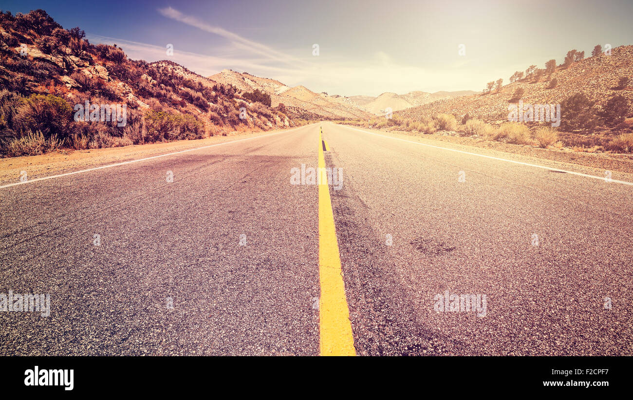 Retro vintage old film style endless country road, travel adventure concept, space for text, USA. - Stock Image