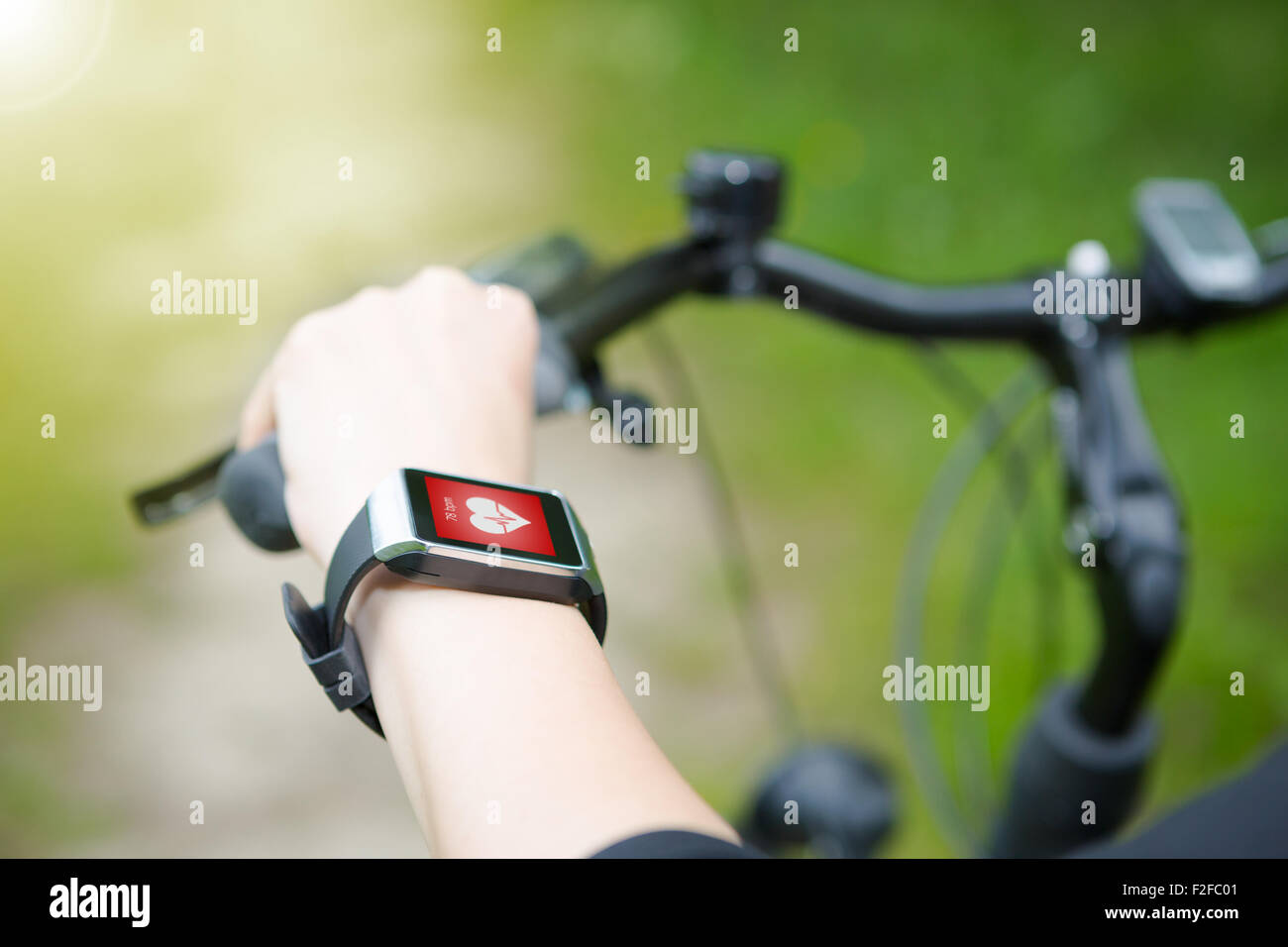 Woman riding a bike with a smartwatch heart rate monitor. Smart watch concept. - Stock Image