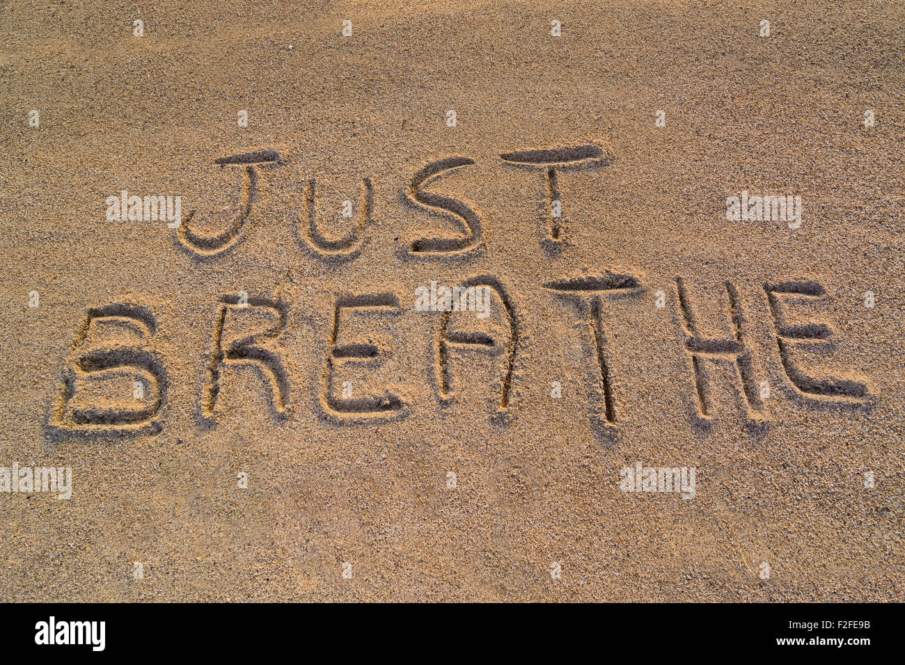 In the picture the words on the sand 'Just breathe'. - Stock Image
