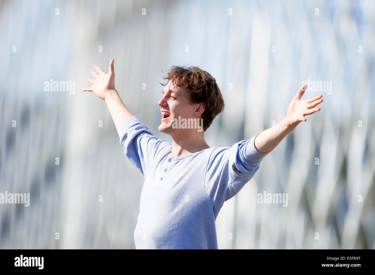 Excited Young Man Stretching out his Arm in Emotion Outdoors - Stock Image