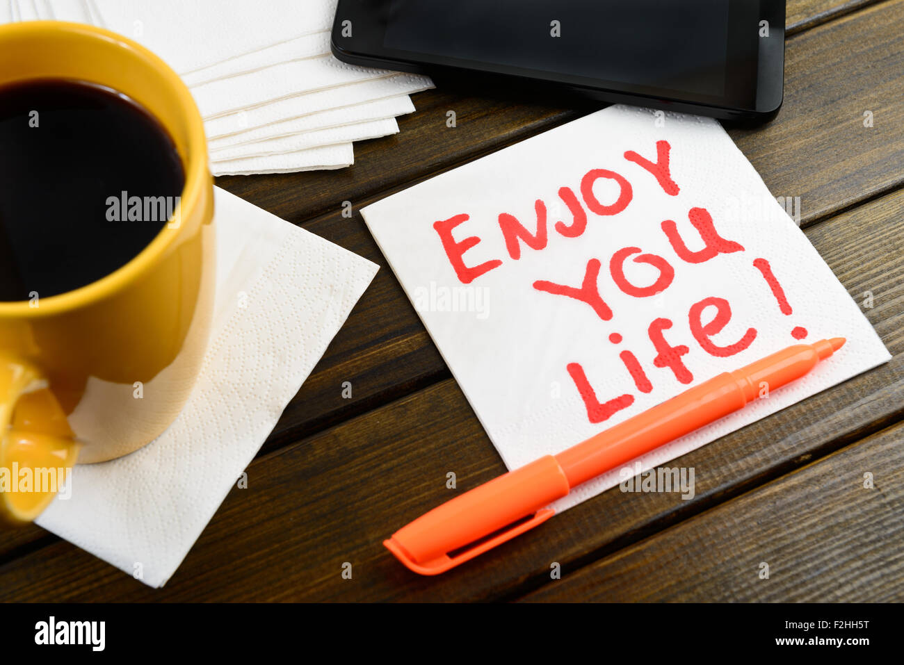 Enjoy your life writing on white napkin around coffee pen and phone on wooden table - Stock Image