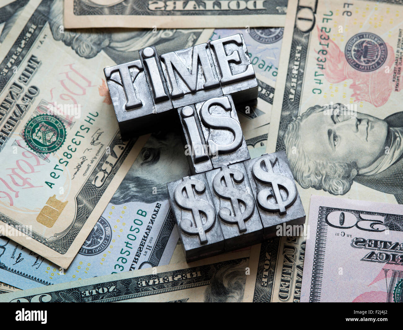 time is money concept made from metallic letterpress type on heap of US dollars - Stock Image