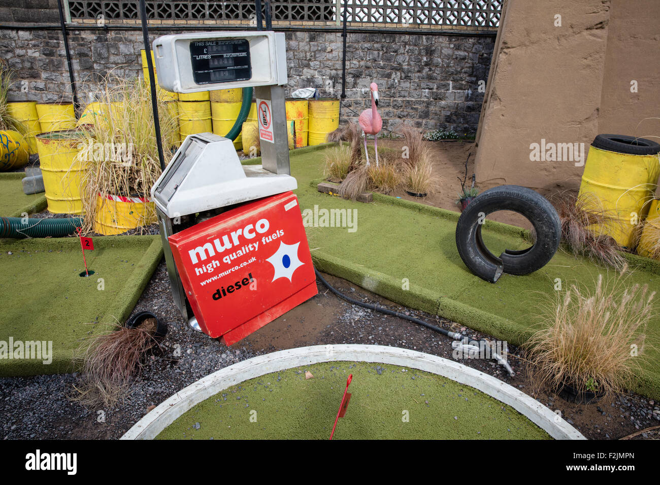 Crazy Gulf course at Banksy's Dismaland in Weston super Mare with battered fuel pump oil drums and old tyres - Stock Image
