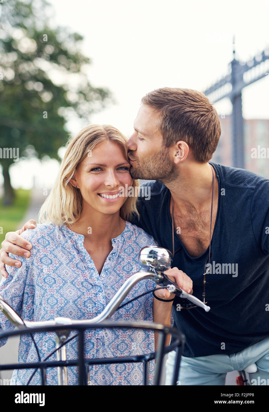 Affectionate young man kissing his girlfriend on the forehead as they enjoy a summer day in the fresh air on their - Stock Image