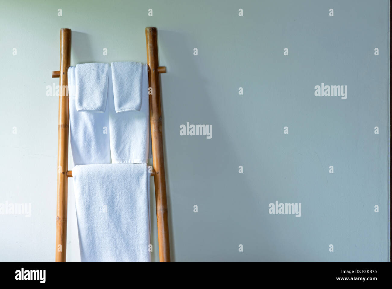 Towels hanging on the bamboo hanger and ready to use Stock Photo