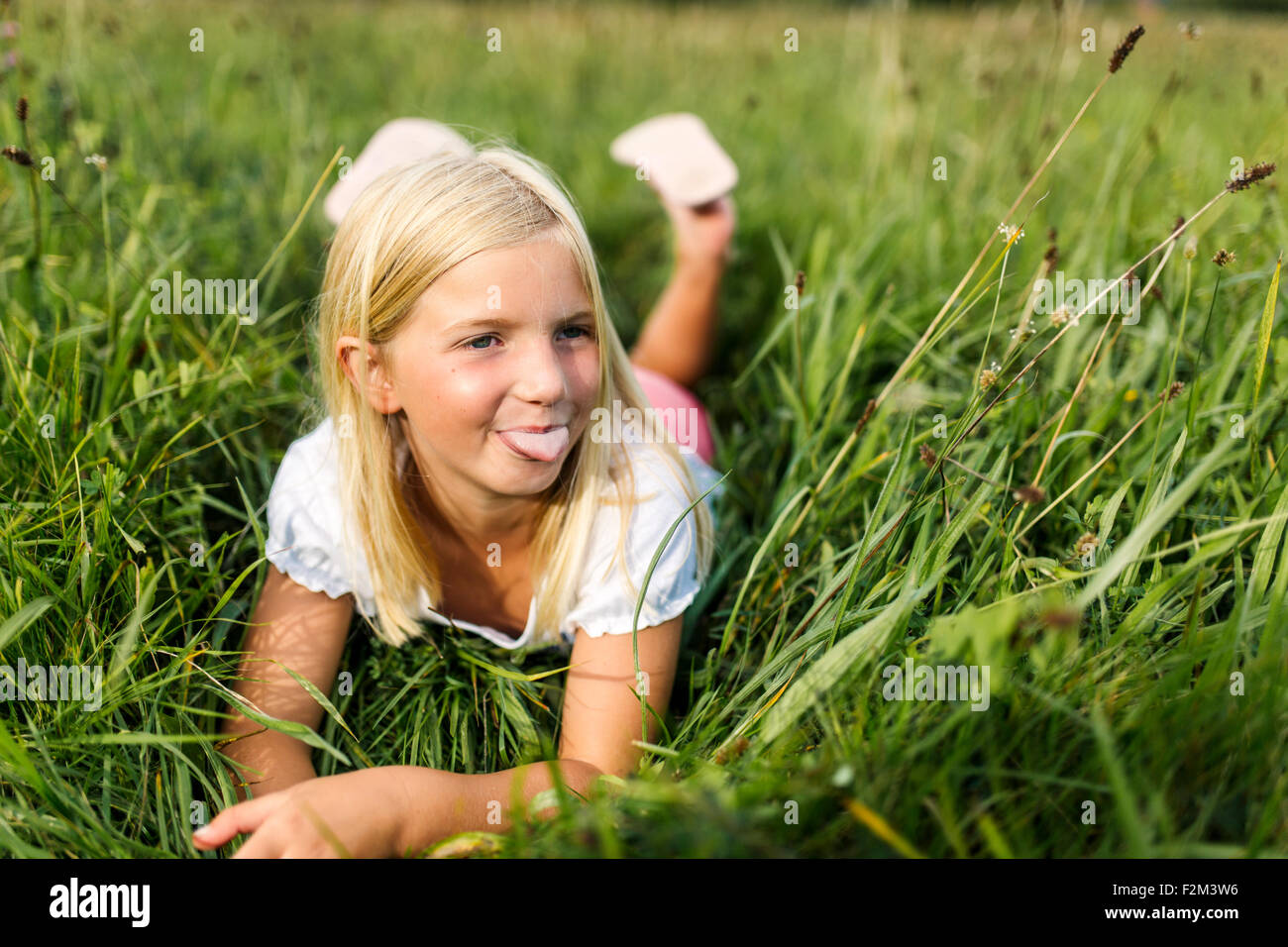 Portrait of girl lying on a meadow sticking out tongue - Stock Image