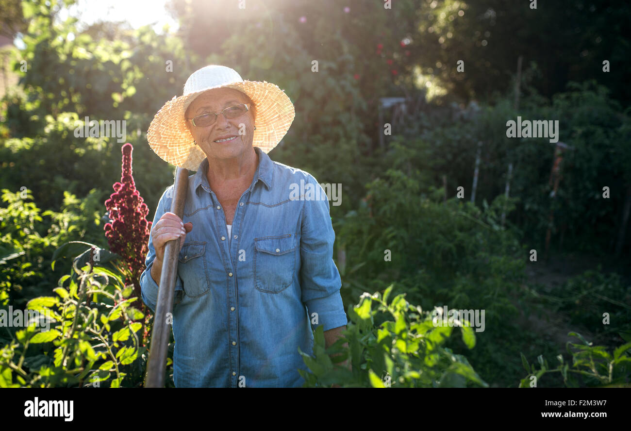 Portrait of smiling senior woman with straw hat in her garden - Stock Image