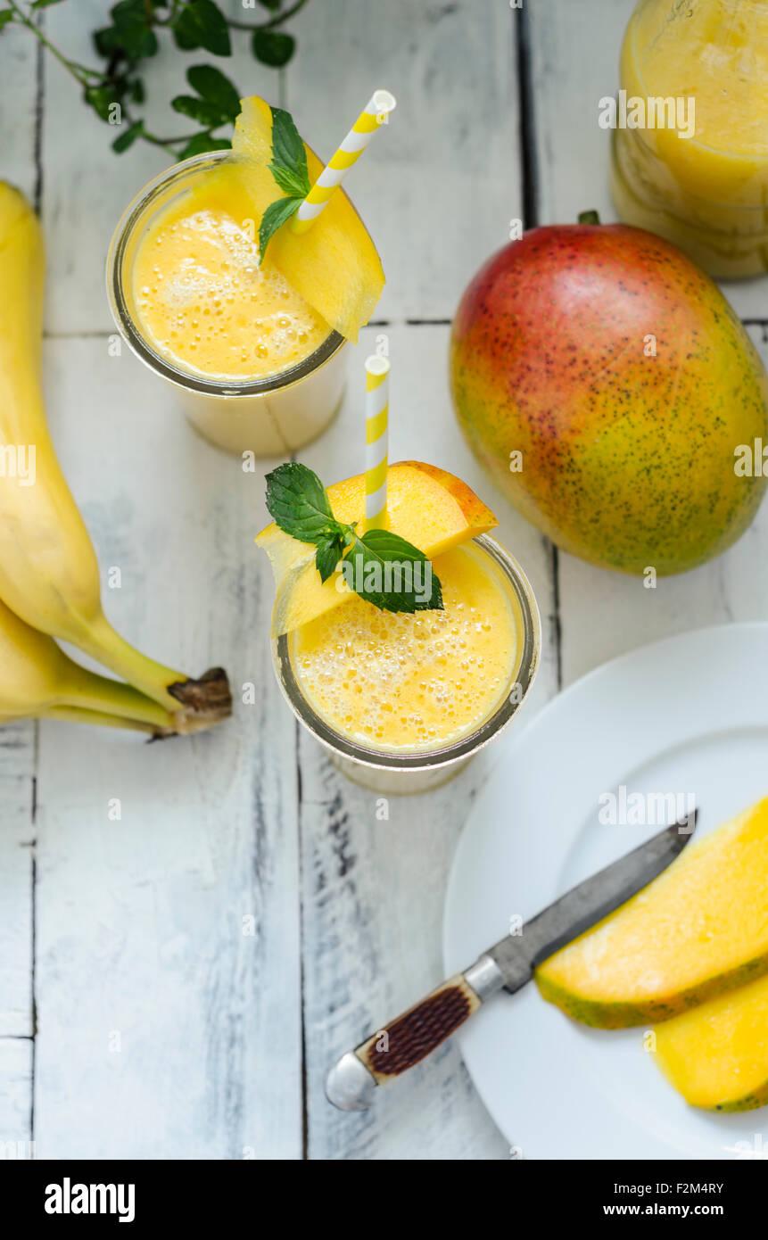 Two glasses of mango banana smoothie - Stock Image