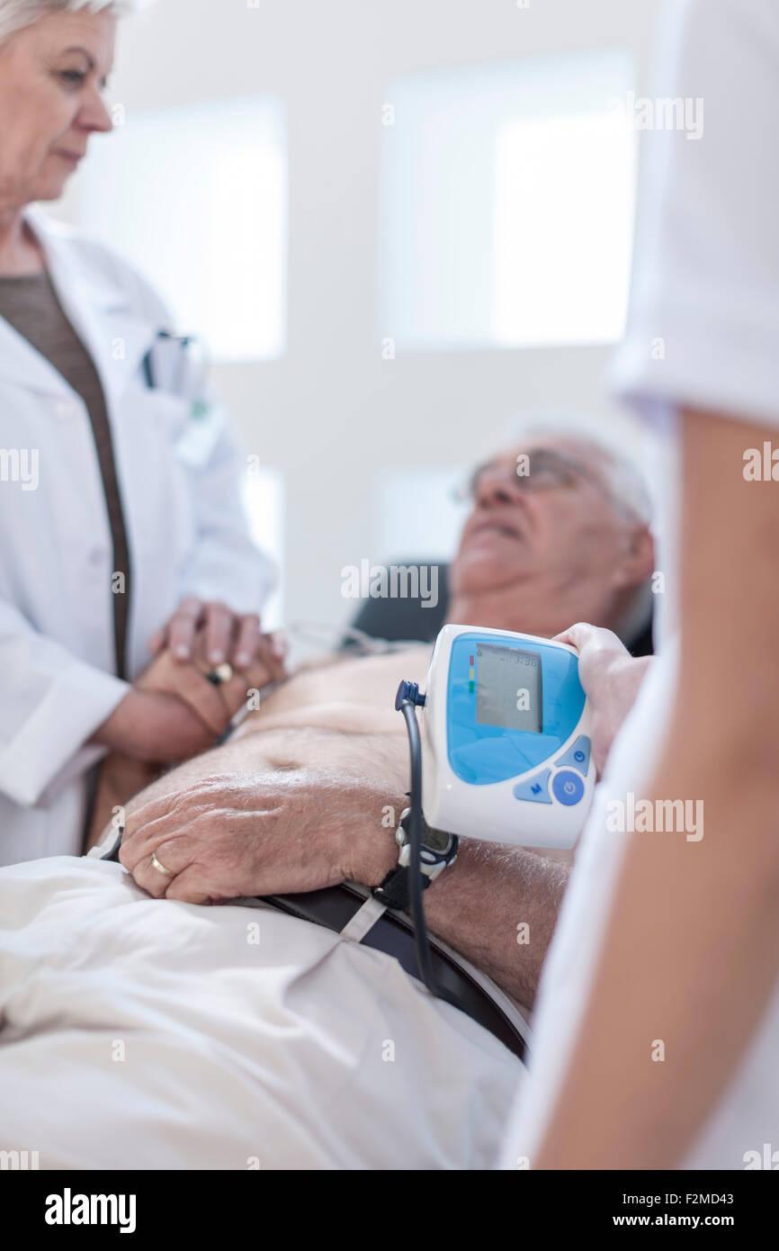 Senior man doing chek up in hospital, looking worried - Stock Image