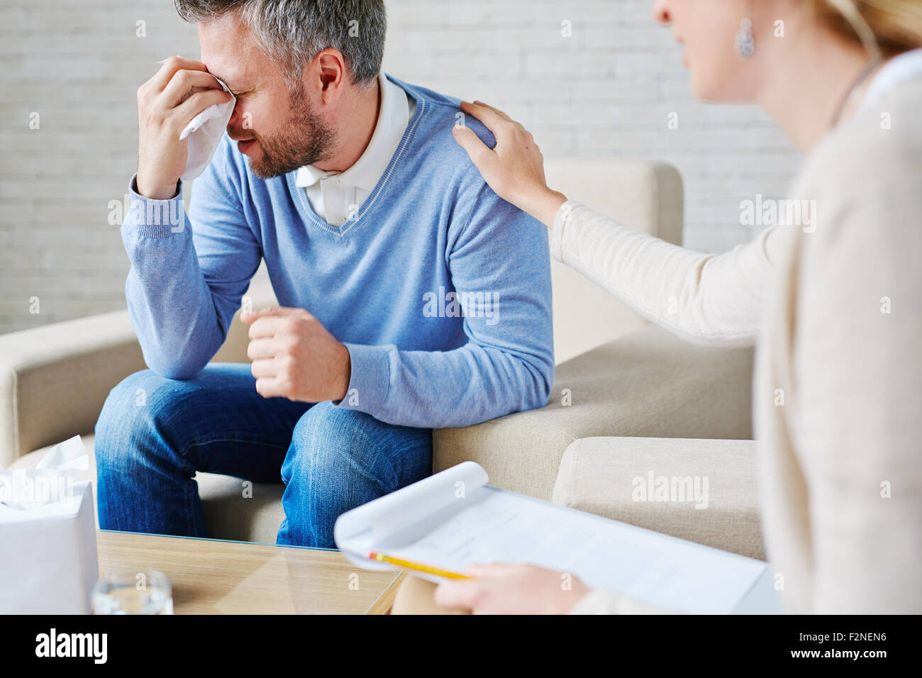 Crying man with handkerchief sitting by his psychologist - Stock Image