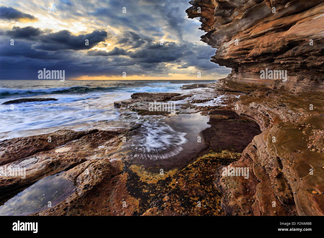 natural sandstone rocks forming high rising landscape at sea edge of coastal line in Sydney, Australia - Stock Image
