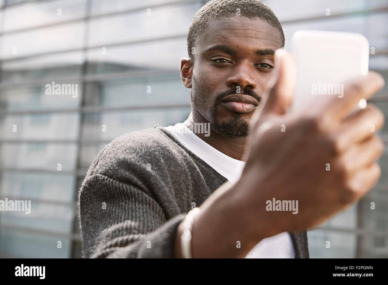 Young man taking a selfie outdoors - Stock Image