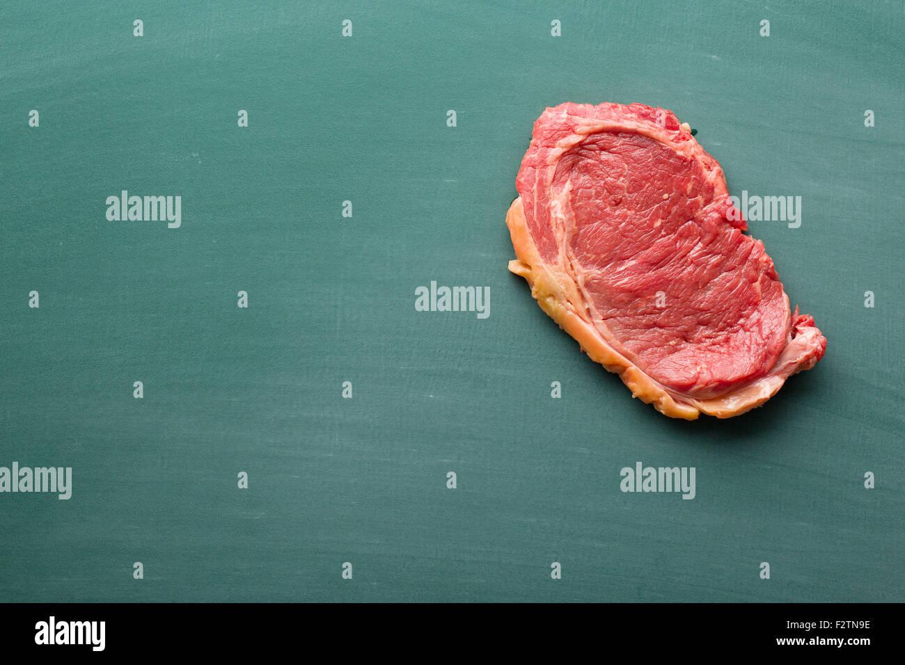 fresh raw beef on chalkboard - Stock Image