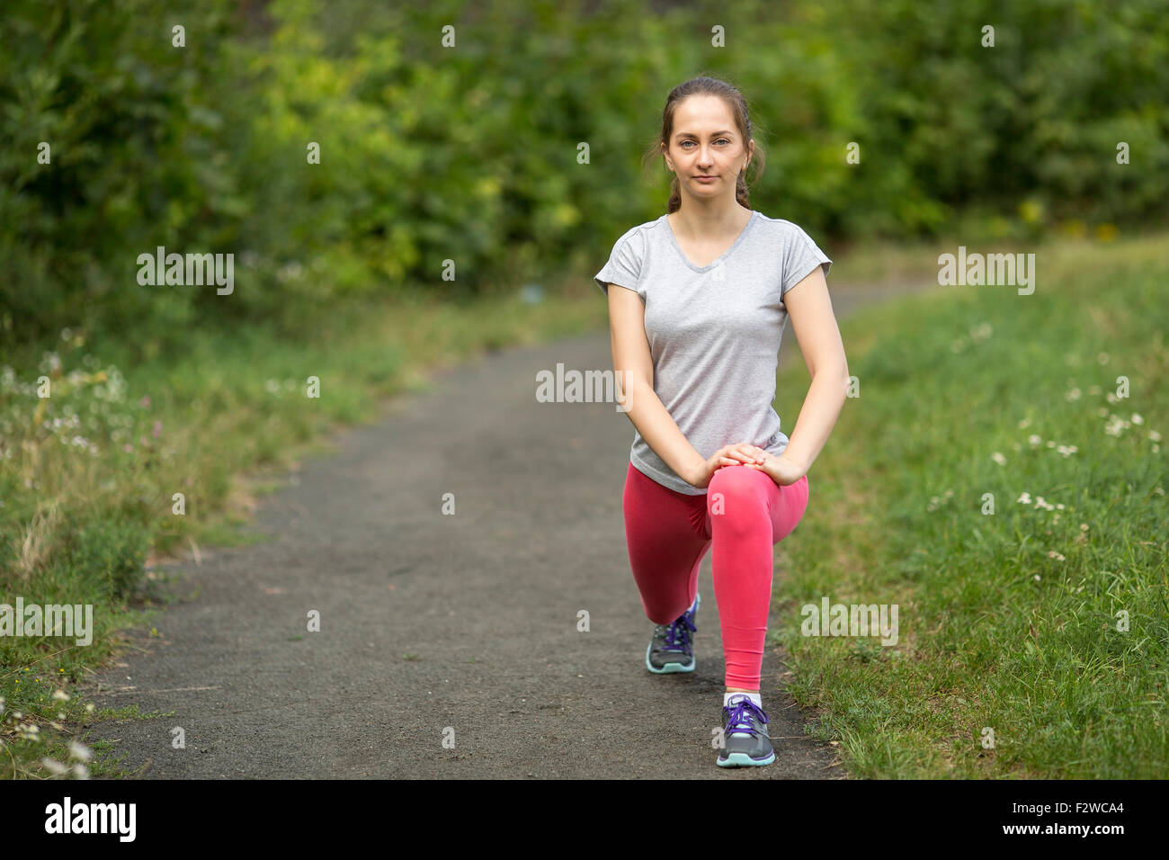 Young sporty girl is warming up outdoors. A healthy lifestyle. - Stock Image