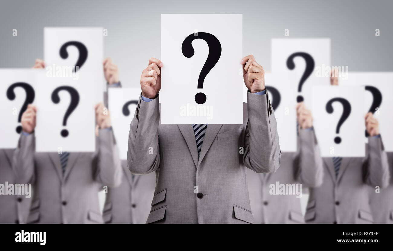 Business colleagues holding question mark signs in front of their faces - Stock Image