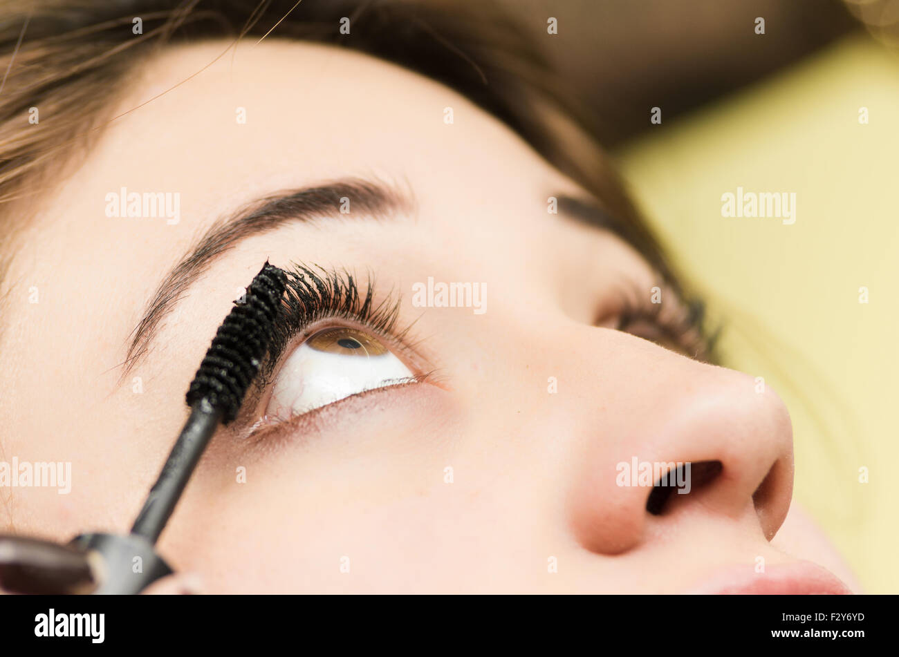 Closeup headshot brunette getting makeup treatment by professional stylist applying mascara on eyelashes - Stock Image