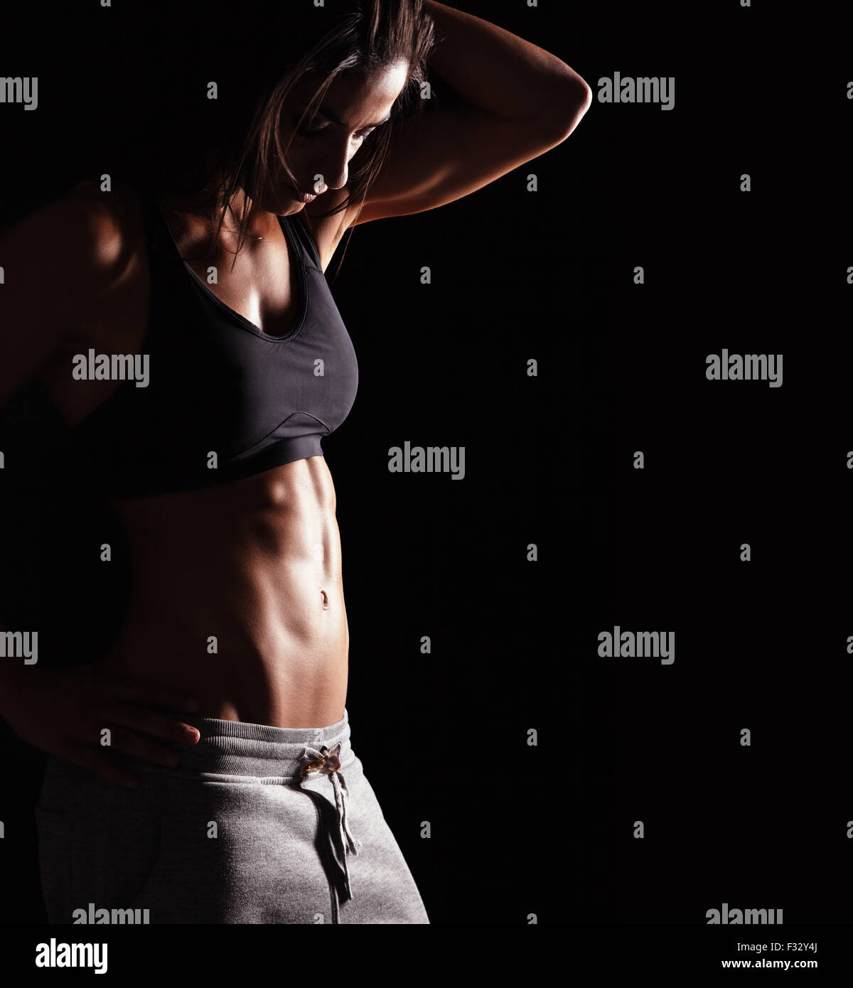 Image of fitness woman in sports clothing looking down. Young female model with muscular body. Horizontal studio - Stock Image