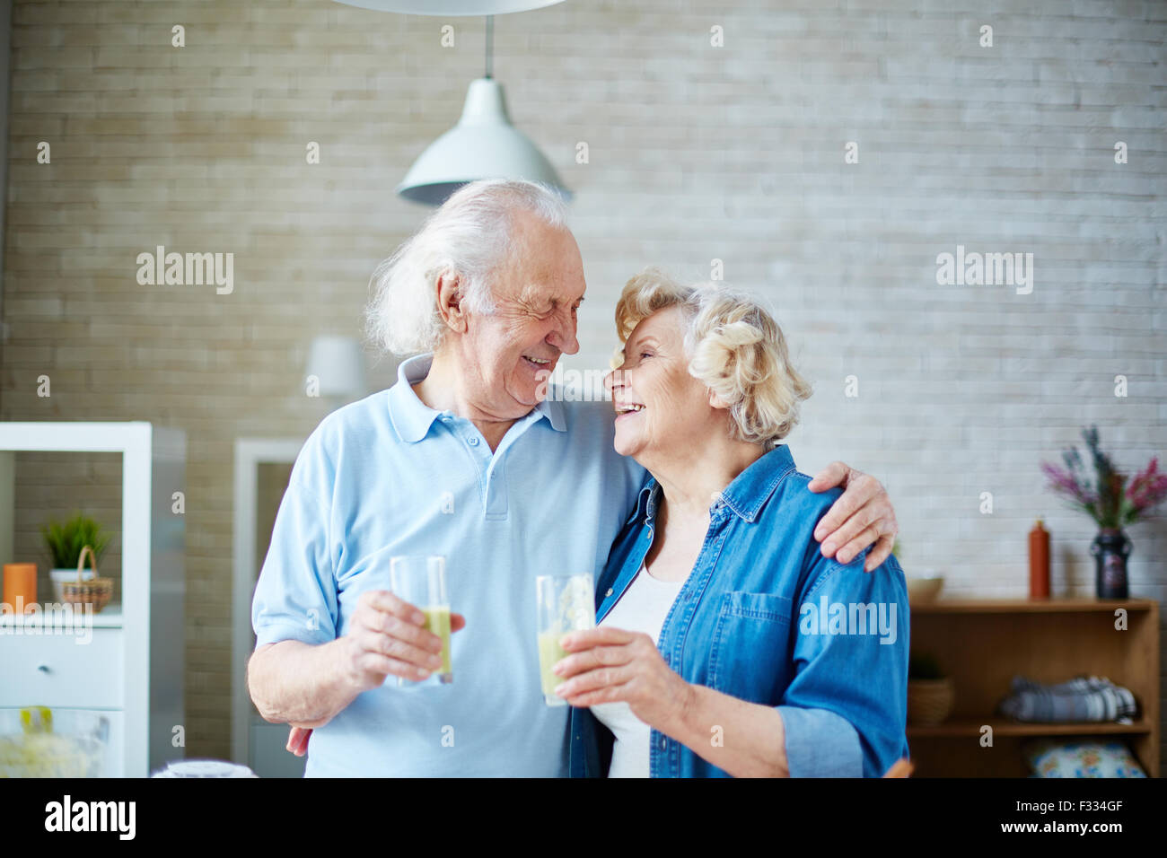 Senior husband and wife holding glasses with healthy homemade fruit drink and looking at one another - Stock Image