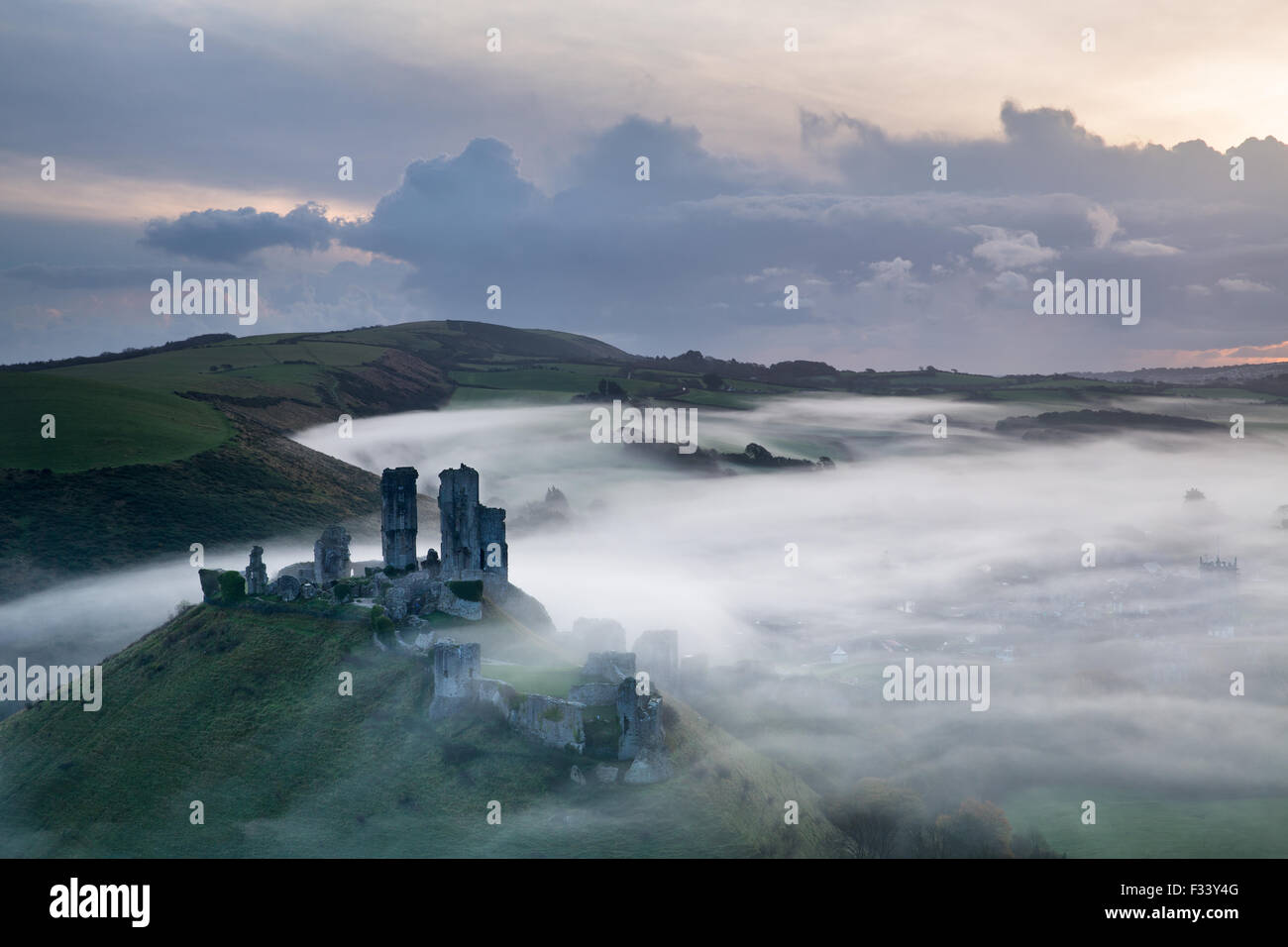 Corfe Castle in the mist at dawn, Dorset, England - Stock Image