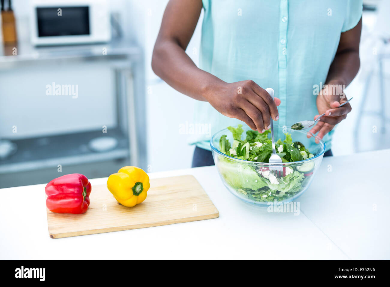 Midsection of pregnant woman having salad - Stock Image