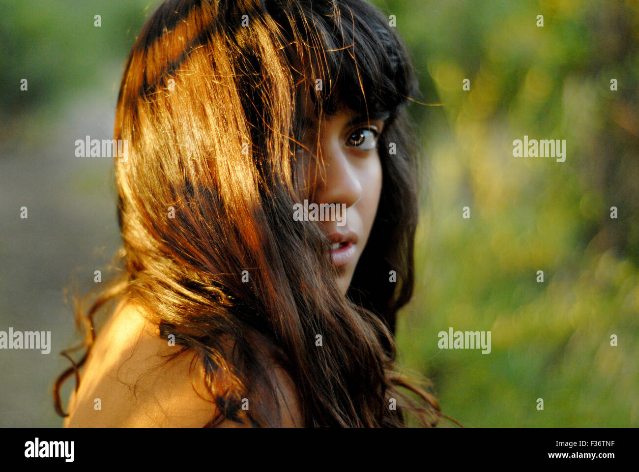Wild girl with green eyes in the middle of the jungle very deep look glare - Stock Image