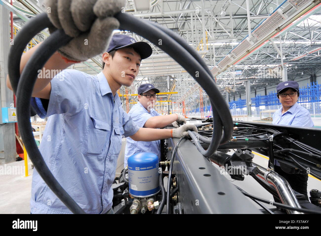(151001) -- XINGTAI, Oct. 1, 2015 (Xinhua) -- Workers work on a production line at a production base of Aviation - Stock Image