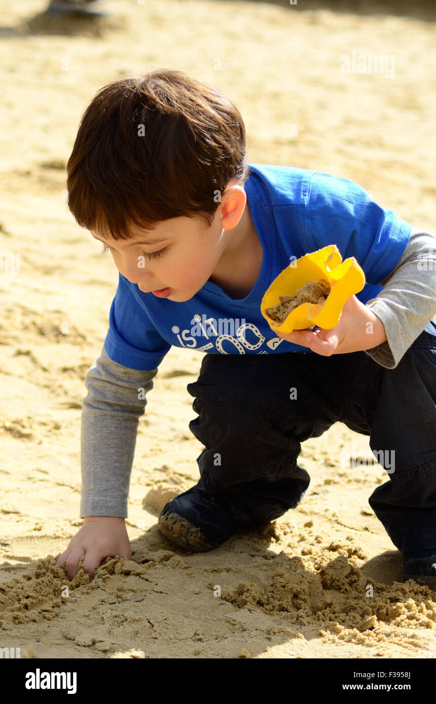 a-young-boy-plays-with-the-sand-in-the-childrens-play-area-in-the-F3958J.jpg